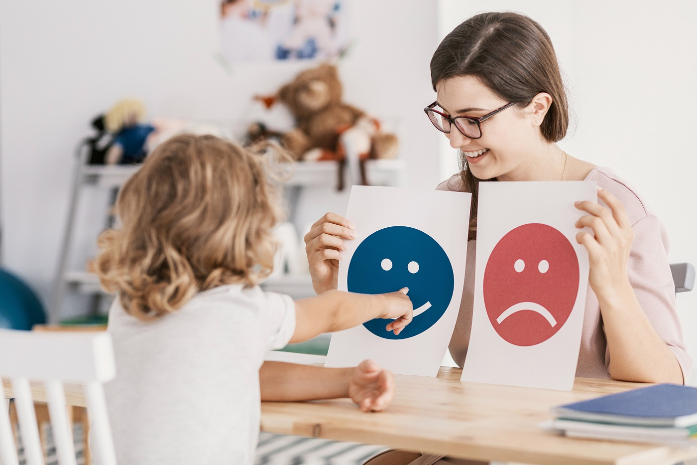 A young child works with a Behavior Specialist - identifying emotions using simple face drawings.